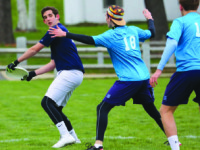 Captain Ben Wishnie-Edwards '16 prepares to huck the disc downfield past two Hotchkiss defenders.