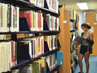A student browses the library bookstacks.