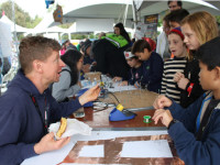 Dr. Travis Feldman, left, teaches children the art of inventing, designing, and tinkering during Maker Faire last weekend.