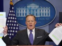 Sean Spicer waves papers as he addresses the press from the White House newsroom.