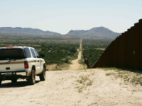 American agents patrol the Mexican border alongside an existing border wall. The United States Department of Homeland Security is responsible for monitoring the borders.