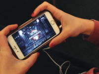 A student streams the tournament on their phone.