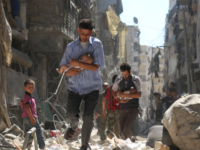 Syrian men carry  children through rubble in Aleppo in September 2016.