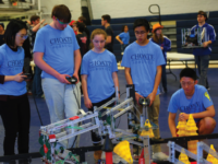 Members of the robotics team test their robot at the competition.